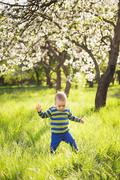 Little child making his first steps in long grass. - stock photo