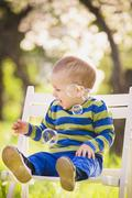 Little cute baby playing with soap bubbles. Boy sitting on white wooden chair - stock photo