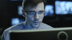 Concentrated male IT professional in glasses is working on a computer in office Stock Footage
