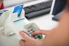 Cropped image of male customer's hand entering pin code on card reader at clo Stock Photos