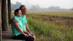 Asian senior couple sitting next to rice field. agricultural business Stock Footage