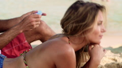 Stock Video Footage of Man applying sunscreen lotion on woman's back at Ipanema beach