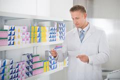 Pharmacist reading label on medicine packet while holding prescription paper  - stock photo