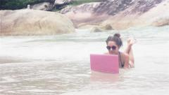 Girl lies on the beach with laptop covering with water Stock Footage