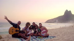 Stock Video Footage of Group of happy friends posing together with guitar on Ipanema beach