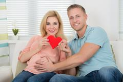 Portrait of happy expecting couple holding heart on sofa at home - stock photo