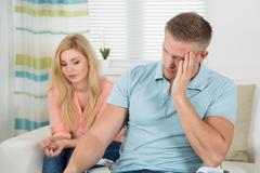 Unhappy young couple having argument at home - stock photo