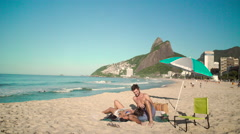 Stock Video Footage of Romantic couple relaxing on Ipanema beach