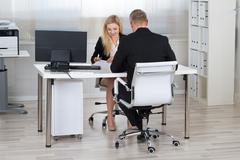 Smiling young businesswoman interviewing male candidate at desk in office Stock Photos
