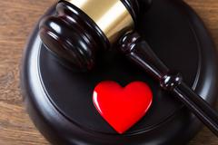 High angle view of mallet and heart on table in courtroom - stock photo