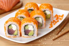 Philadelphia sushi roll with tuna, avocado, cream cheese, cucumber and tobiko - stock photo