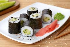 Maki sushi roll with cucumber, wasabi, ginger and nori seaweed - stock photo