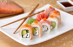 Rainbow dragon sushi roll with salmon, avocado, soft cheese, cucumber and tobiko - stock photo