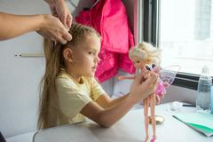 A girl playing with dolls until my mother weave braid of hair Kuvituskuvat