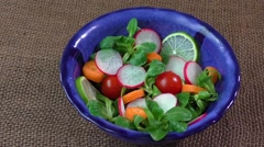 Bowl of fresh vegetable salad on jute table cloth Stock Footage