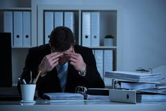 Stressed accountant sitting with head in hand while working late in office - stock photo