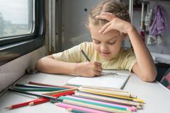 Stock Photo of Six-year girl joyfully draws pencils in second-class train carriage