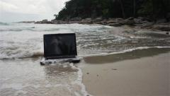 Laptop is covering with water on the beach Stock Footage