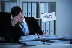 Stressed accountant holding help sign at desk while working late in office Stock Photos