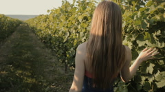 Charming slim girl in a strapless dress walks along the vineyards Stock Footage