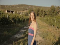 Slim girl in strapless dress posing in rows of vineyards Stock Footage