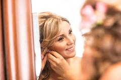 Woman putting on diamond earrings. Caucasian beauty lady trying and shopping Kuvituskuvat