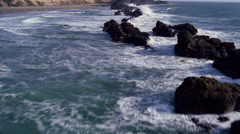 Looking down onto rocks pounded by ocean waves Stock Footage