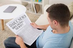 High angle view of mid adult man reading breaking news on newspaper at home Kuvituskuvat