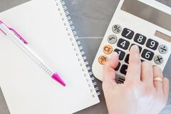 Hand with calculator and notepad Stock Photos