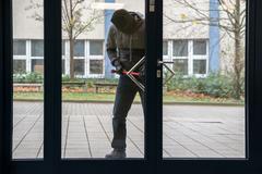 Full length of hooded man using crowbar to open glass door Kuvituskuvat