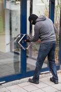Hooded man using crowbar to open glass door Kuvituskuvat