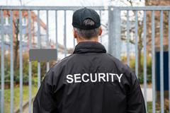 Rear view of mature security guard standing in front of gate Stock Photos