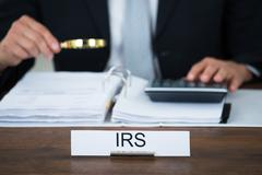 Midsection of tax auditor examining documents with magnifying glass at table  - stock photo