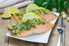 Baked salmon with macadamia-cilantro crust on a white plate Stock Photos