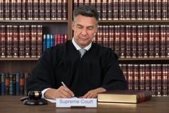Mature male judge writing on paper at table in courtroom - stock photo