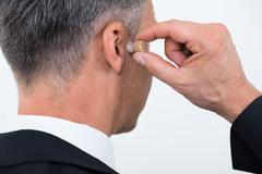 Stock Photo of Rear view of businessman inserting hearing aid in ear over white background