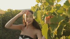 Beautiful brunette in a strapless dress posing next to the vine Stock Footage