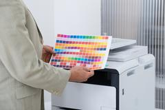 Midsection of businessman holding multi colored paper by printer in office - stock photo