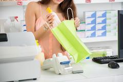 Midsection of young saleswoman putting cleansing product into paper bag at ch Stock Photos