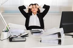 Tensed female accountant sitting with head in hands at desk in office Stock Photos