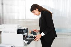 Side view of young businessman fixing cartridge in printer machine at office - stock photo