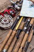 fishing rods and reels on wooden boards - stock photo