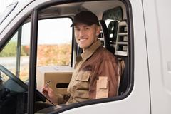 Portrait of confident delivery man making checklist in truck - stock photo