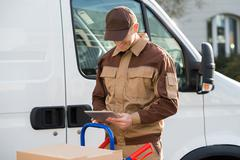 Portrait of smiling delivery man holding digital tablet against truck Stock Photos