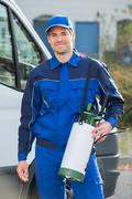 Stock Photo of Portrait of confident pest control worker with pesticide against truck