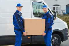 Portrait of happy delivery men carrying cardboard box while standing against  Kuvituskuvat