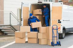 Young delivery men unloading cardboard boxes from truck on street Stock Photos