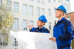 Young male architect showing something to colleague while analyzing blueprint - stock photo
