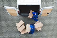 Stock Photo of Directly above shot of delivery men unloading cardboard boxes from truck on s