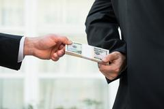 Cropped image of businessman taking bribe from partner outdoors - stock photo